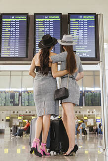 Two fashionable young women at the airport terminal checking the arrival departure board - LJF01191