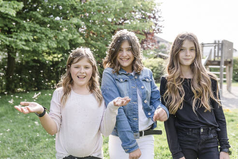 Portrait of three happy girls surrounded by dandelion seeds - STBF00506