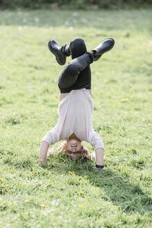 Girl doing a headstand on a meadow - STBF00515