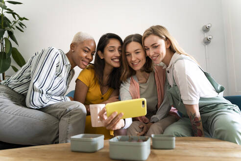 Four women sitting on couch taking a selfie - AFVF04475