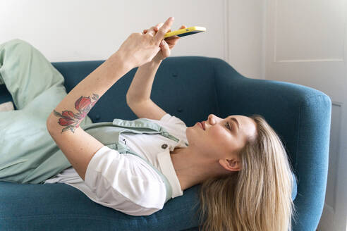 Young woman lying on couch using cell phone - AFVF04487