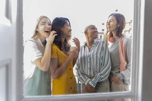 Four happy women standing on balcony - AFVF04490