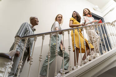 Four happy women walking upstairs in staircase - AFVF04508