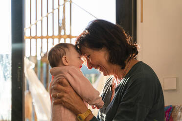 Grandmother holding baby girl, head on head and smiling - GEMF03357