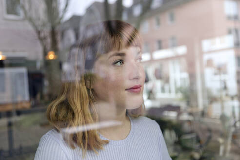 Portrait of young woman with nose piercing looking out of window - FLLF00366