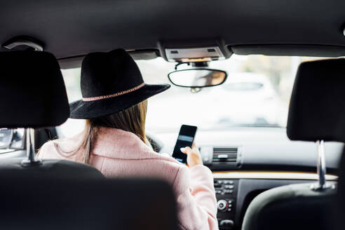 Businesswoman using smartphone during drive - CJMF00202