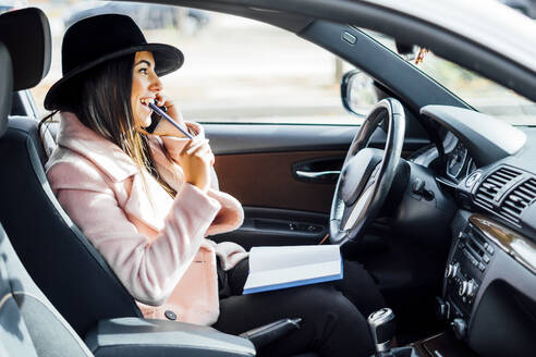 Businesswoman using smartphone in the car, notebook on lap - CJMF00205