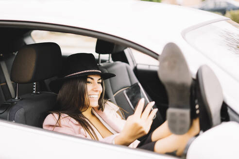 Businesswoman using smartphone and taking a selfie in the car - CJMF00208