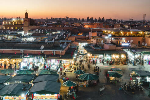 High angle view of people shopping at Marrakesh market during night in city - CAVF70779
