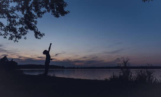 Silhouette boy holding sparkler while standing at lakeshore against sky during dusk - CAVF70842