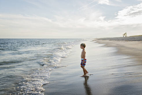 Side view of shirtless boy looking away while standing at Tobay Beach against sky - CAVF70878