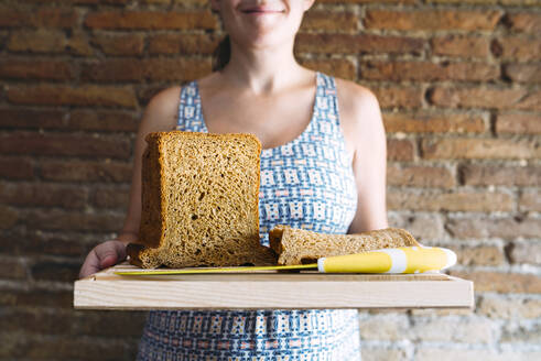 Midsection of woman holding cutting board with bread and kitchen knife against brick wall - CAVF70893