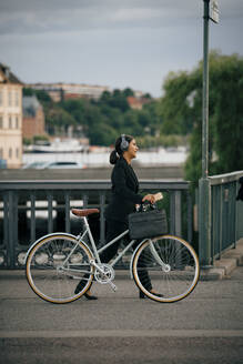 Side view of businesswoman walking with bicycle on bridge in city - MASF15519