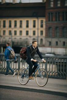 Full length of businessman riding bicycle on bridge - MASF15522