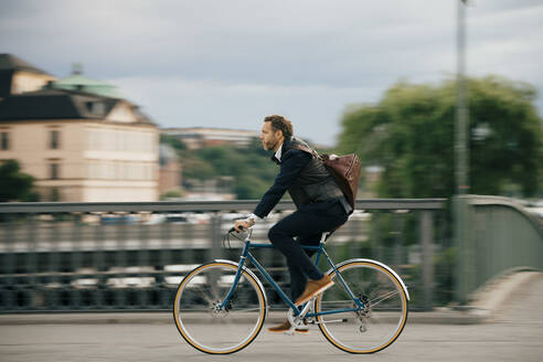 Full length of confident businessman riding bicycle on bridge - MASF15525
