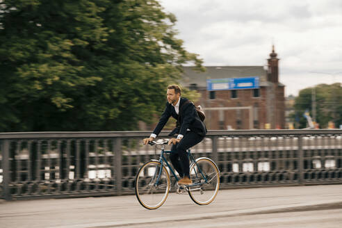 Full length of confident businessman riding bicycle on city street - MASF15528