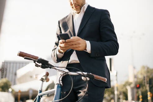 Midsection of businessman using mobile phone while standing by bicycle in city - MASF15540