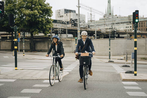 Smiling businessman and businesswoman riding bicycles on road in city - MASF15552
