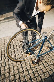 High angle view of businessman repairing bicycle on footpath in city - MASF15555