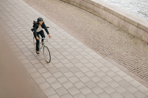 High angle view of businesswoman riding bicycle on footpath - MASF15573