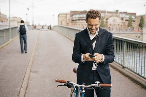 Smiling businessman using mobile phone while standing with bicycle on bridge in city - MASF15576
