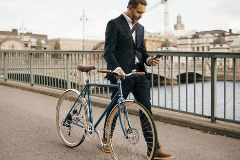 Confident businessman using smart phone while walking with bicycle on bridge in city - MASF15579
