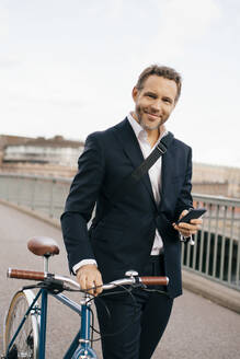 Portrait of confident businessman holding mobile phone while walking with bicycle on bridge in city - MASF15582