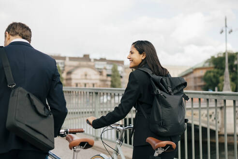 Smiling businesswoman looking at businessman while walking with bicycles on bridge in city - MASF15588