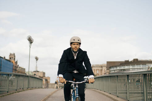 Confident businessman riding bicycle on bridge in city against sky - MASF15591