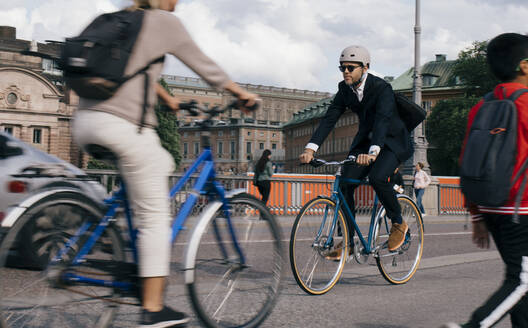 Full length of businessman riding bicycle on street in city - MASF15597