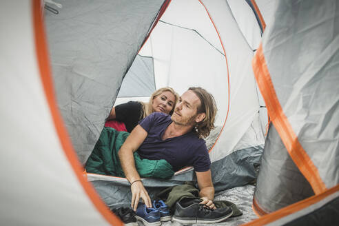 Couple peeking though tent while leaning in sleeping bag during camping - MASF15615