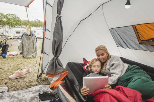 Girl watching digital tablet while lying with mother in tent at campsite - MASF15621