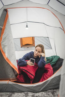 Teenage girl using smart phone while sitting in tent at camping site - MASF15624
