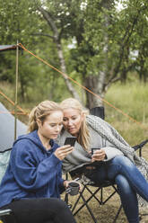 Mother and daughter looking at smart phone while having coffee in campsite - MASF15636