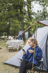 Teenage girl using mobile phone while having coffee against tent - MASF15639