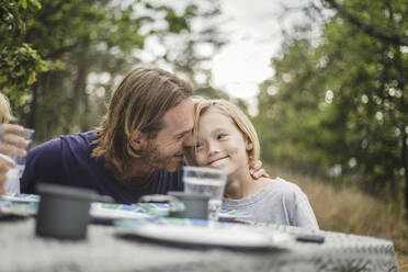 Affectionate father embracing daughter at table in campsite - MASF15645