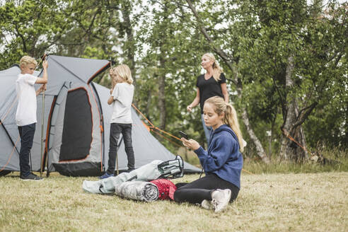 Teenager text messaging on mobile phone while family pitching tent - MASF15651