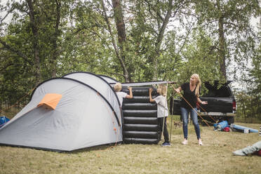 Mother talking to children carrying mattress in tent at camping site - MASF15654