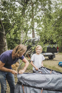 Father and daughter talking while pitching tent at camping site - MASF15660