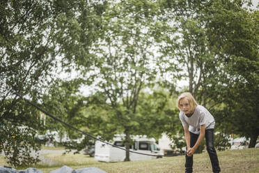 Girl preparing tent in forest at camping site during vacation - MASF15666