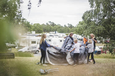 Family pitching tent together at camping site during summer vacation - MASF15669