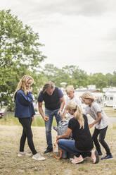 Family looking at woman unpacking tent at camping site - MASF15672
