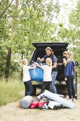 Children assisting parents in unloading luggage from car trunk at camping site - MASF15675