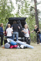 Camping family unloading luggage from car trunk at forest - MASF15678