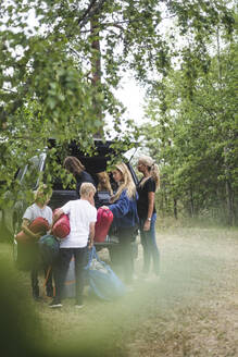 Family unloading luggage from car at camping site - MASF15681