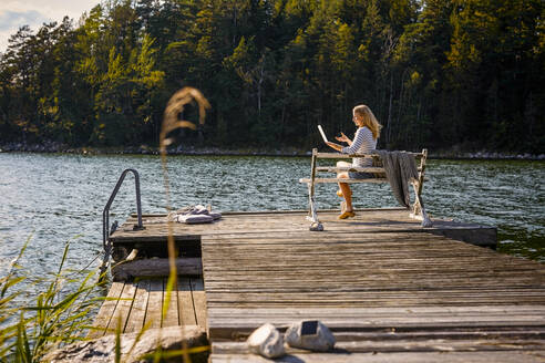 Mid adult woman doing video call on laptop while sitting on bench over wooden pier against lake in forest - MASF15738