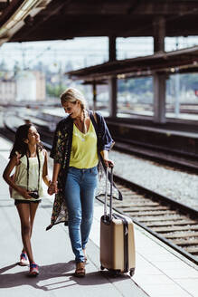 Smiling mother and daughter with luggage talking while walking at station - MASF15798