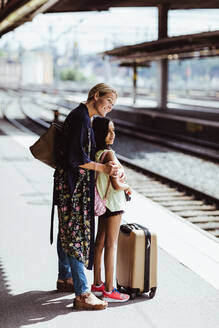 Smiling mother and daughter waiting on platform at train station - MASF15801