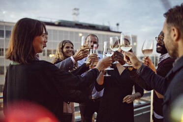 Business coworkers toasting wineglasses while celebrating in office party on terrace - MASF15885