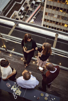 High angle view of business colleagues talking while enjoying office party after work - MASF15891